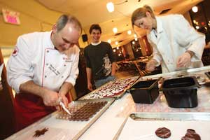 Oliver de Volpi, McGill's executive chef and vedrana Gergov, chef's helper, show students how to make truffles at Bishop Mountain Hall. / Photo: Owen Egan