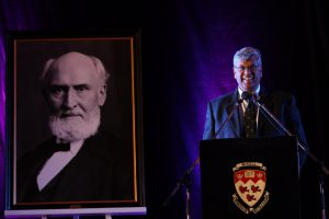 Under the watchful eye of Macdonald College founder, McGill Associate Vice Principal and Dean of the Faculty of Agricultural and Environmental Sciences Chandra Madramooto addresses the audience at the annuak Founder's Day ceremoy. / Photo: Owen Egan.