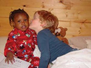 Five-year-old Max Engle-Warnick gives his new sister Esther a kiss just days after her arrival to Montreal from Haiti. Three-year-old Esther was adopted by economics professor Jim Engle-Warnick and his wife Jayne.