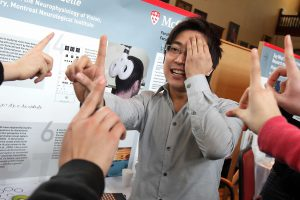 James Tsui, a PhD candidate in the Faculty of Medicine who works at the Montreal Neurological Institute, gives onlookers a quick demonstration of visual perception and the tricks our mind can play on us. / Photo:: Owen Egan