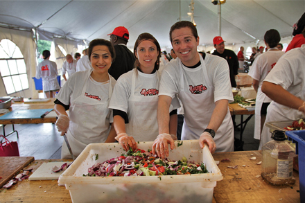 (From left to right) Volunteers Rezwan Ghassemi, John Tabaka and Marjolaine Ross help make some of the more than 2,000 pounds Greek salad that was made during the Tomato Fiesta. Most of the food was donated to local charities. / Photo: Neale McDevitt