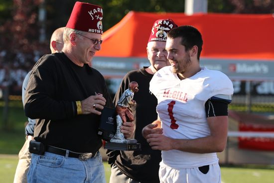 Rookie quarterback Pierre-Luc Dussault receives McGill's offensive player-of-th- game honours from Mike Keys, chairman of the 27th annual Montreal Shrine Bowl. / Photo: Derek Drummond