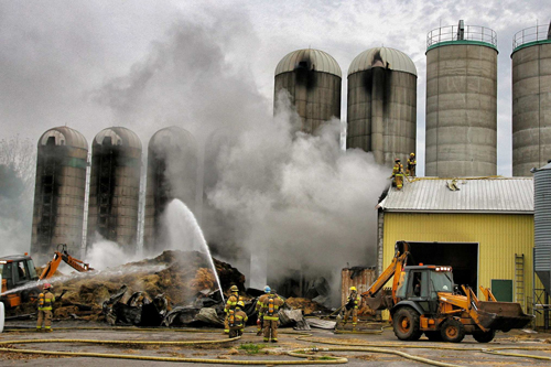 Firefighters battle the blaze that destroyed the feed storage facility at Macdonald Campus Farm earlier today. / Photo: Neale McDevitt