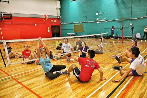 Participants in Community Engagement Day's sitting volleyball event engage in a rally. / Photo: Neale McDevitt