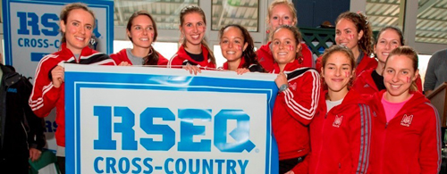 Members of McGill's provincial champion cross country running team pose with the championship banner. / Photo courtesy of Université de Sherbrooke