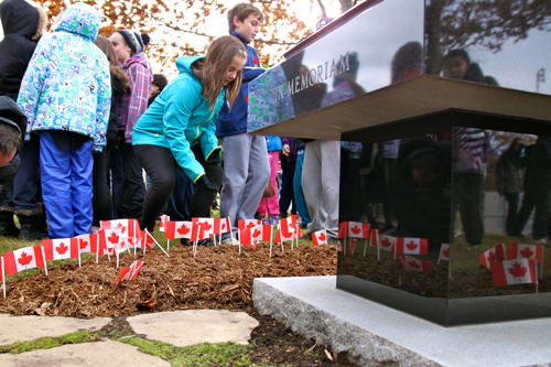 Children plant Canadian flags around the Mac memorial. / Photo: Neale McDevitt