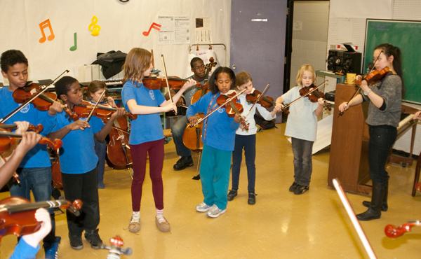 Viva!Sistema musicians concentrate on their instruments at a recent rehearsal. / Photo: Robin Michetti