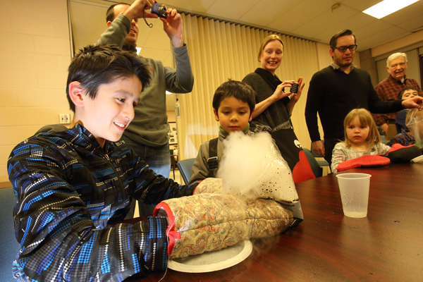 Félix Bélair, 11, makes a homemade comet using dry ice, water and dirt as his six-year-old brother Xavier looks on. / Photo: Owen Egan