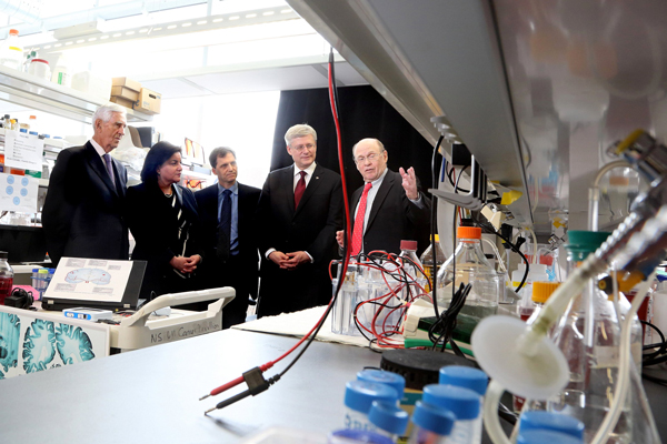From left to right: André Chagnon, philanthropist; Naomi Azrieli of the Azrieli Foundation; Dr. Benoit Mulsant and Prime Minister Stephen Harper get the VIP tour of Dr. Nahum Sonenberg's lab on May 1. / Photo: Owen Egan