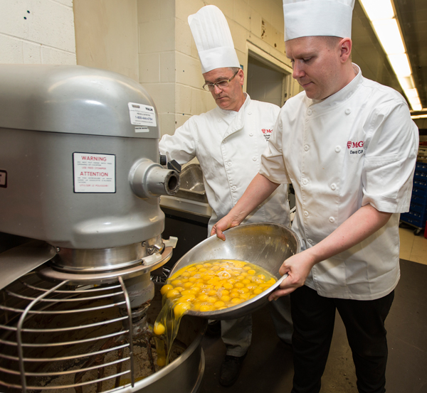 David Côté (right) pours a batch of fresh Macdonald Campus farm eggs into the New Residence Hall's industrial mixer as pastry chef Sylvain Favreau looks on. / Photo: Leslie Schachter