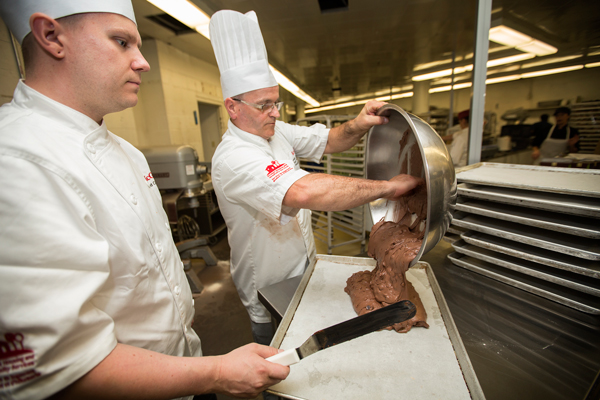Pastry chef Sylvain Favreau pours brownie mix while David Côté is poised to spread the mix / Photo: Leslie Schachter