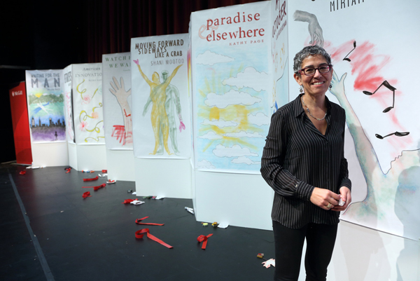 Artist Sara Heppner-Waldston and the posters she made on stage for each of the longlisted books as they were announced. / Photo: Owen Egan
