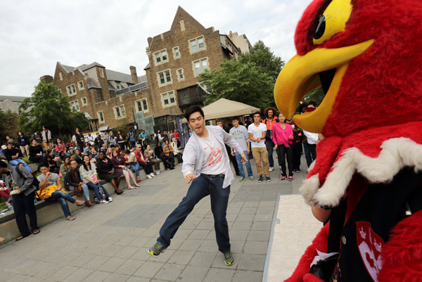 A member of the McGill Student Street Dancers performs for the crowd, as Marty the Martlet looks on. / Photo: Owen Egan