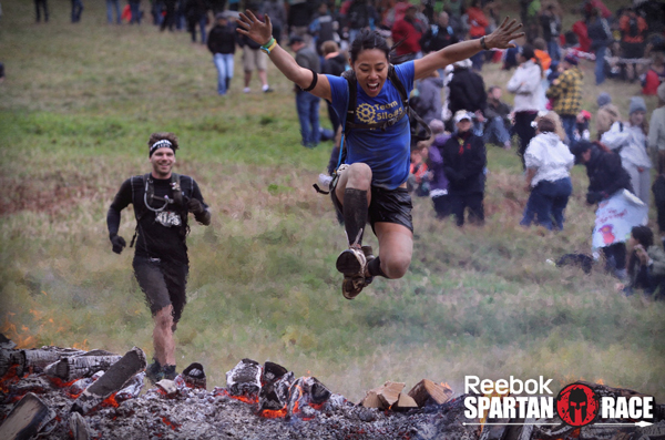 Victoria Leenders-Cheng leaps over a fire pit during a recent Spartan race.