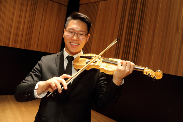 Byungchan (Chan) Lee with the covetted Golden Violin, made of pewter and gold plate and donated by philanthropist Seymour Schulich in 2006. / Photo: Owen Egan