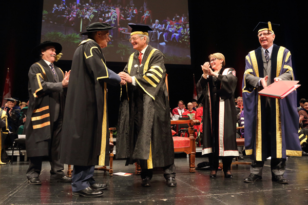 McGill's newly installed Chancellor Michael Meighen (wearing the red tie), shakes hands with his predecessor, Arnold Steinberg, during Fall 2014 Convocation ceremonies. / Photo: Owen Egan