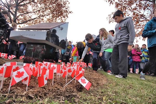 Local school children plant Canadoan flags around the War Memorial. / Photo: Neale McDevitt