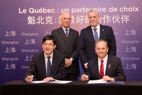 McGill's Vice-Dean of Life Sciences, Philippe Gros (seated right), and signs the agreement with Wen Chen, Dean, Fudan School of Public Health as Occupational Health Professor Paul Héroux (standing, left) and Quebec Premier Phillippe Couillard look on. / Photo: Patrick Alleyn