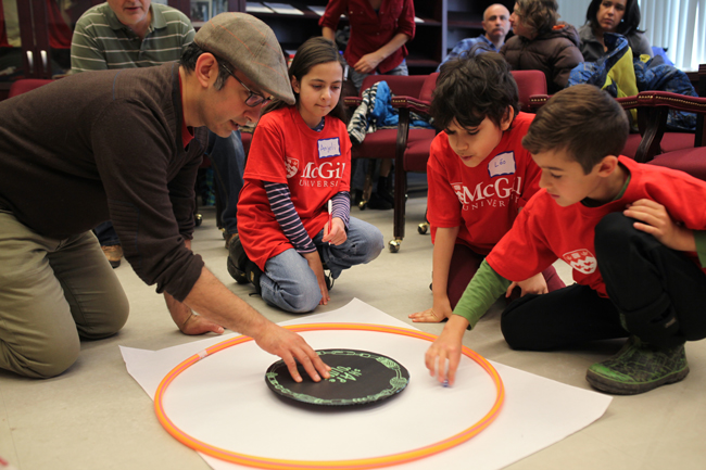 Anurag Dhir (left), SEDE's Community Engagement Coordinator, helps students perform an experiment during a workshop given by McGill's Astrophysics and Cosmology Group. / Photo: Andrew Kittredge