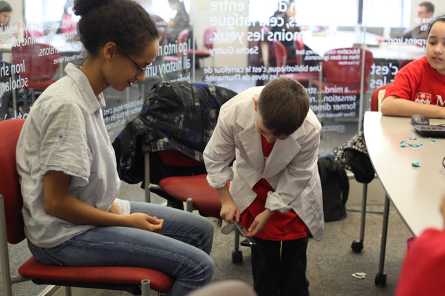 A young boy learns about reflexes during a workshop put on by Medicine students. / Photo: Andrew Kittredge