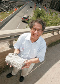 Saeed Mirza holding crumbling concrete at the Pine-Park interchange in downtown Montreal, currently undergoing renovation