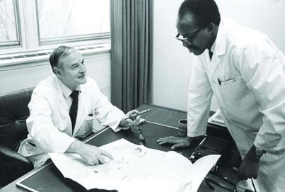 Dr. Douglas Cameron, director of McGill's educational program with University College Nairobi, speaks with one of the Kenyan doctors who studied at McGill. Credit: McGill University Archives (PR031373)