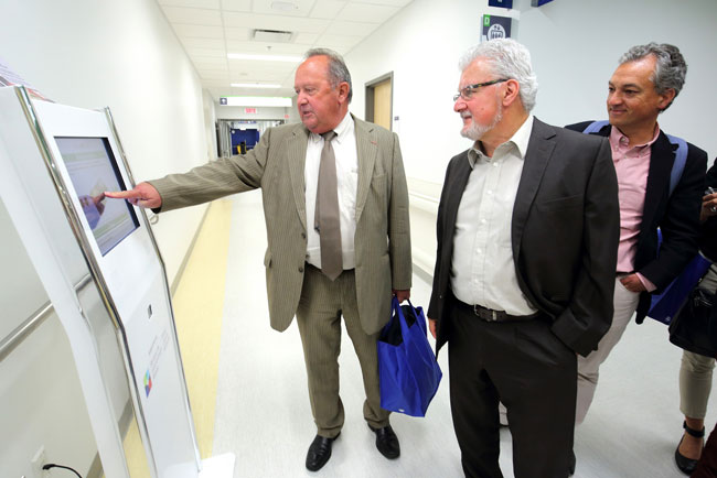 Jean Pierre DeWitte (left), director general of the CHU de Poitiers, tests out the new RCN self-check-in kiosks being piloted at the MUHC.  / Photo: Owen Egan
