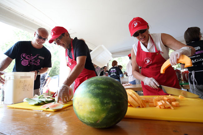 Principal Suzanne Fortier and Ollivier Dyens, Deputy Provost (Student Life and Learning) help chop some of the 3,000 kilos of fresh fruit that went into the smoothie as Mathieu Laperle, Senior Director of Student Housing and Hospitality Services, looks on. / Photo: Owen Egan