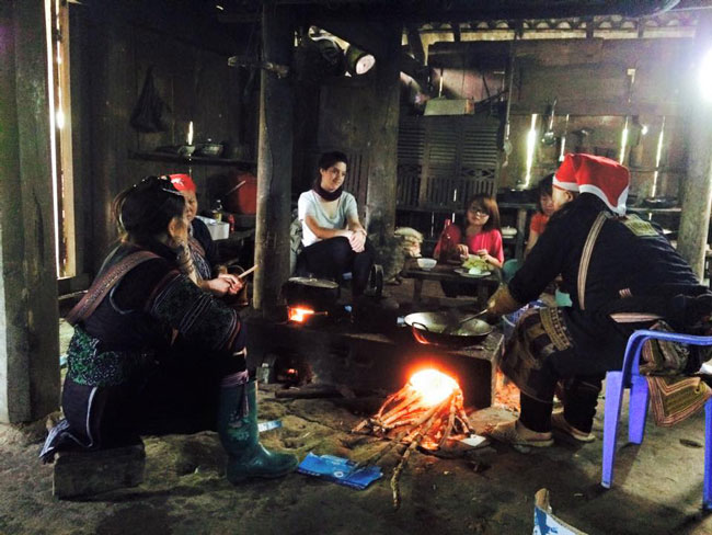 Enrica Ferrarotti eats lunch with a Red Dao minority family in a village near Sapa, North Vietnam.