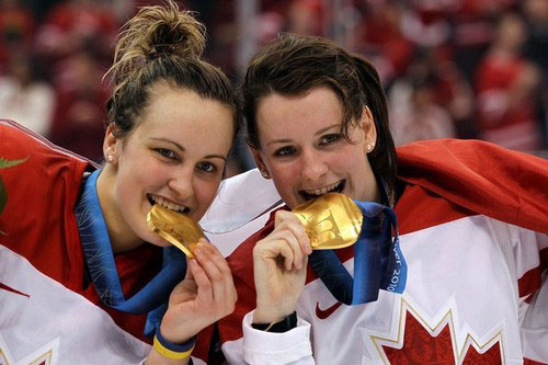 Catherine Ward, right, takes a bite out of her gold medal at last year's Sochi Olympics.