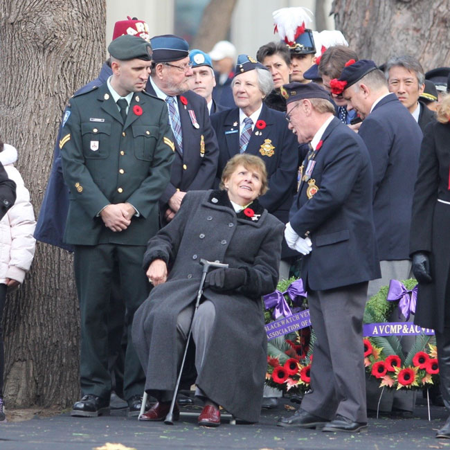 Therese Guerette, the mother of slain soldier Warrant Officer Patrice Vincent, talks to veterans prior to laying a wreath at the cenotaph. / Photo: Neale McDevitt
