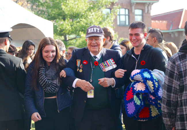 A veteran is escorted from today's Remembrance Day ceremonies at Macdonald Campus by students from nearby Macdonald High School. / Photo: Neale McDevitt