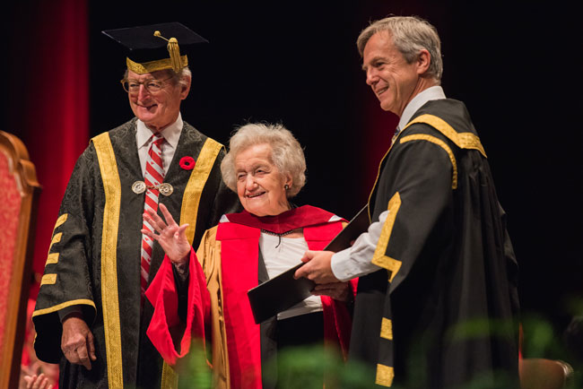 Brenda Milner accepts her Honorary Degree, Doctor of Laws, from Robert Thirsk, Chancellor of the University of Calgary. Michael A. Meighen, McGill's Chancellor  looks on. / Photo: Alison Slattery Photography.