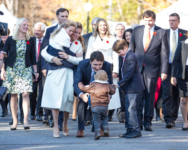 Justin Trudeau arrives at Rideau Hall yesterday morning with his wife, Sophie Grégoire, their children and the soon-to-be-sworn-in cabinet ministers. Here, the couple's son Hardrien demands a lift from dad. / Photo: Adam Scotti