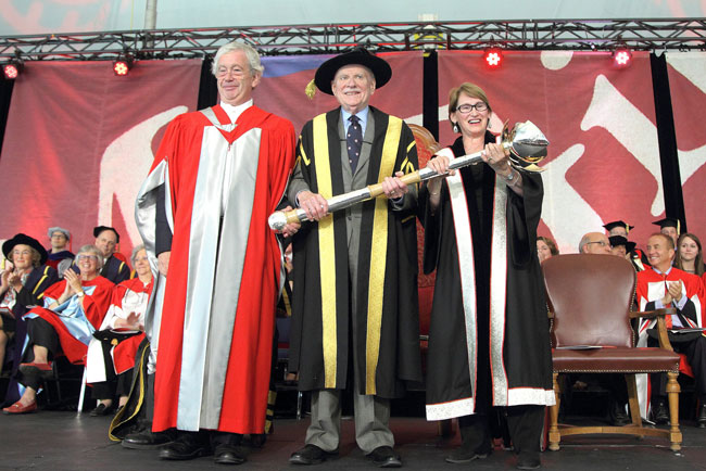 Sir Timothy O'Shea (left), Principal and Vice-Chancellor of the University of Edinburgh, presents Chancellor H. Arnold Steinberg with McGill's new ceremonial mace. / Photo: Owen Egan