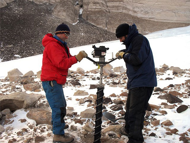Denis Lacelle of University of Ottawa (left) and Alfonso Davila of NASA/SETI (right) operate a motorized ice drill to obtain cores in ice-cemented ground in University Valley. / Credit NASA/Chris McKay