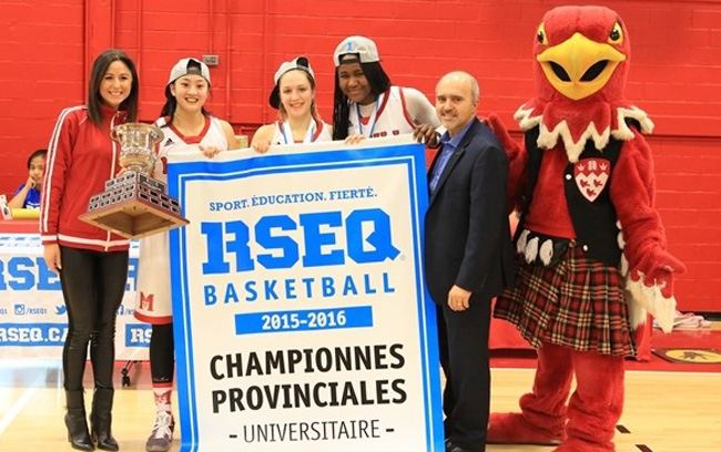 McGill players Dianna Ros, Gabriella Hebert and Mariam Sylla accept the team's fifth-straight RSEQ championship banner. / Photo: Derek Drummond