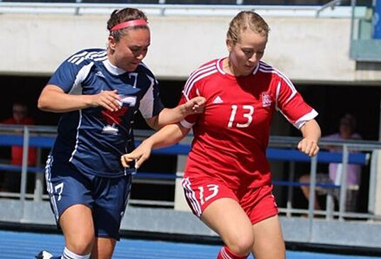 McGill striker Audrey-Ann Coughlan (#13) fends off a U of T player. / Photo courtesy of U of T Athletics and Recreation