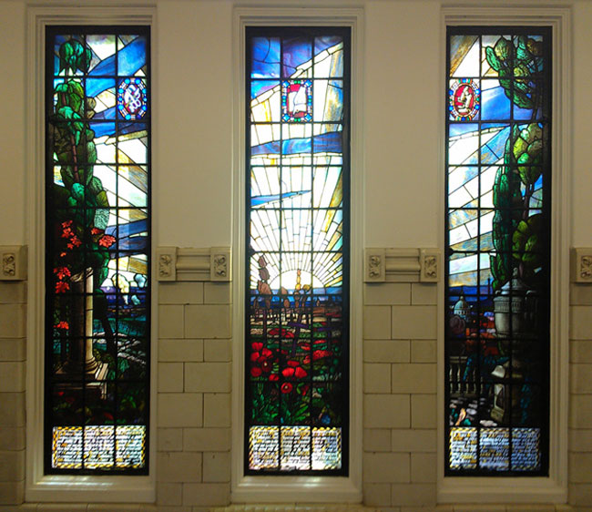 The three panes of a stained glass window in the Strathcona Building commemorate three McGill professors who lost their lives in the Great War. The jeweled plaques in the upper section of each pane symbolize their special interests. In the left pane is a plaque with a surgeon's scissors, scalpel and bandages; in the middle pane a plaque with a quill and book, and in the right pane a microscope.