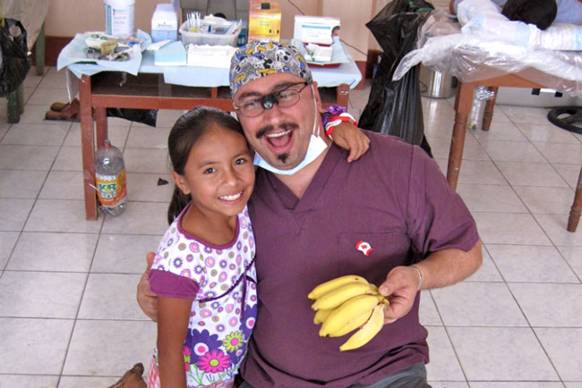 McGill's Dr. Gerard Melki is rewarded for his hard work in  a mobile dental clinic in Shanao, a remote village in Panama, with some bananas from the family garden. / Photo courtesy of Dr. Gerard Melki