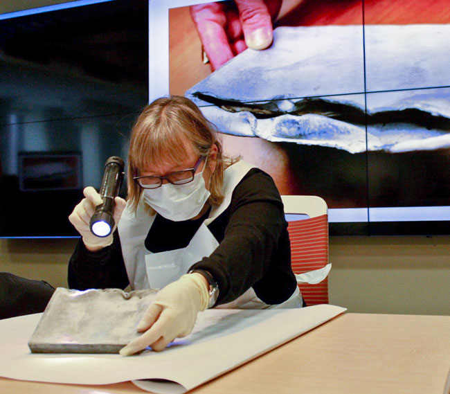 Dressed in protective clothing to guard against mold spores and lead particles, Chantal Emond, Conservator, examines the Roddick Gates time capsule in front of a small audience of some 25-30 curious McGillians.