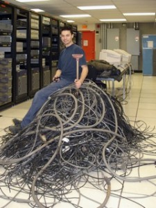 Contractor Pascal Perron of the State Group declares victory over reams of dead cabling he helped pull from under the McGill Data Centre. / Photo: Quan Nguyen