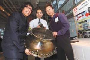 Professor Stephen Yue, Chair, Department of Mining and Materials Engineering (left), Ahmad Rezaeian, Postdoctoral fellow, Mining and Materials Engineering  (centre) and Wilson Wong, Master candidate, Mining and Materials Engineering (right), with part of a jet engine's combustion chamber from their display for the research project Cold spray – hot stuff in aerospace materials engineering. / Photo: Owen Egan
