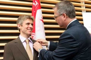 Andrew Reader (left) receives his Canada Research Chair pin from Gary Goodyear, Minister of State (Science and Technology). / Photo: Owen Egan