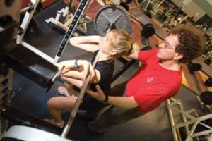 Strength coach Claude Hebert spots Heather McCurdy (4th year Physical Education and Health Education) for a set of front squats. / Photo: Owen Egan