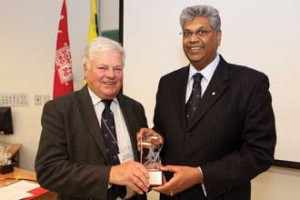 Marc Bieler receives a gift of James McGill crystal from Faculty of Agricultural and Environmental Sciences Dean Chandra Madramootoo. / Photo: Owen Egan