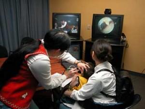 Une audiologiste fait l'examen du tympan d'un enfant au Nunavik. L'image est ensuite envoyée a un médecin de l'Hôpital de Montréal pour enfants.