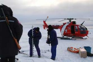 Researcher Bruno Tremblay prepares an auger to drill into an ice floe to insert a sonar to measure ice growth and melt. In the foreground, the helicopter pilot carries a gun to ward off polar bears. Photo courtesy of Bruno Tremblay