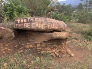 A cryptic warning greets travellers on the road to the Ikafe Refugee Settlement in Northwestern Uganda. / Photo: Justin Dubois